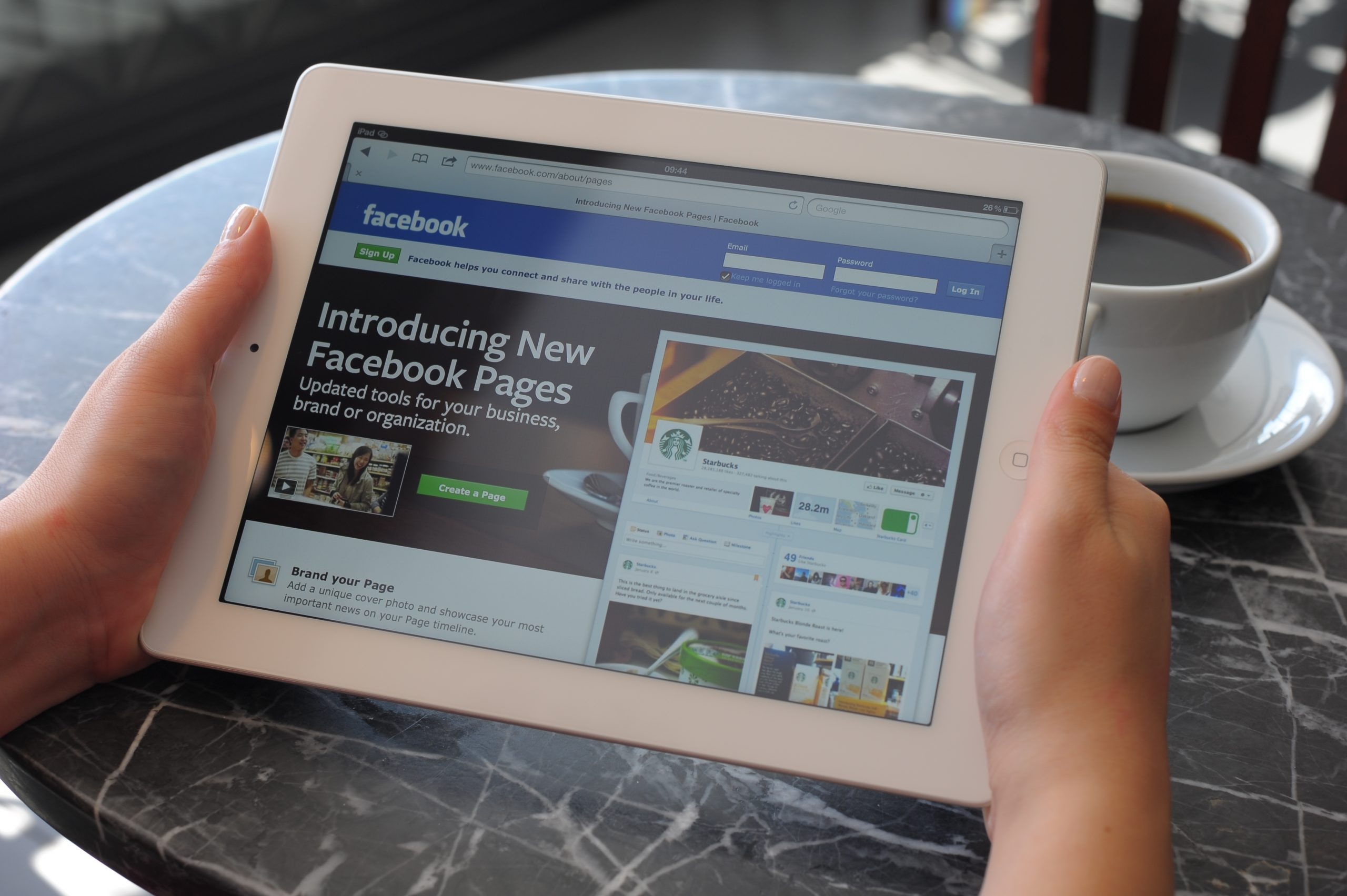 "Astanbul, Turkey - April 16, 2012: Woman hands holding The New iPad displaying ""Introducing New Facebook Pages"" page on Facebook in a coffee shop. The third generation iPad is a touchscreen tablet pc produced by Apple Inc. The new iPad as known as iPad 3."