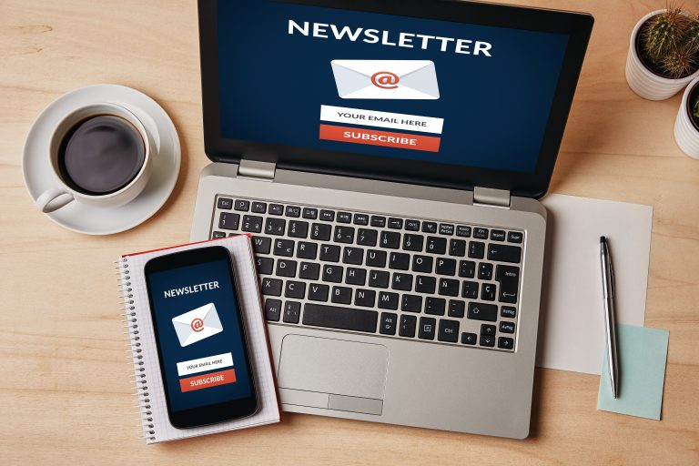 Subscribe newsletter concept on laptop and smartphone screen over wooden table. All screen content is designed by me. Flat lay