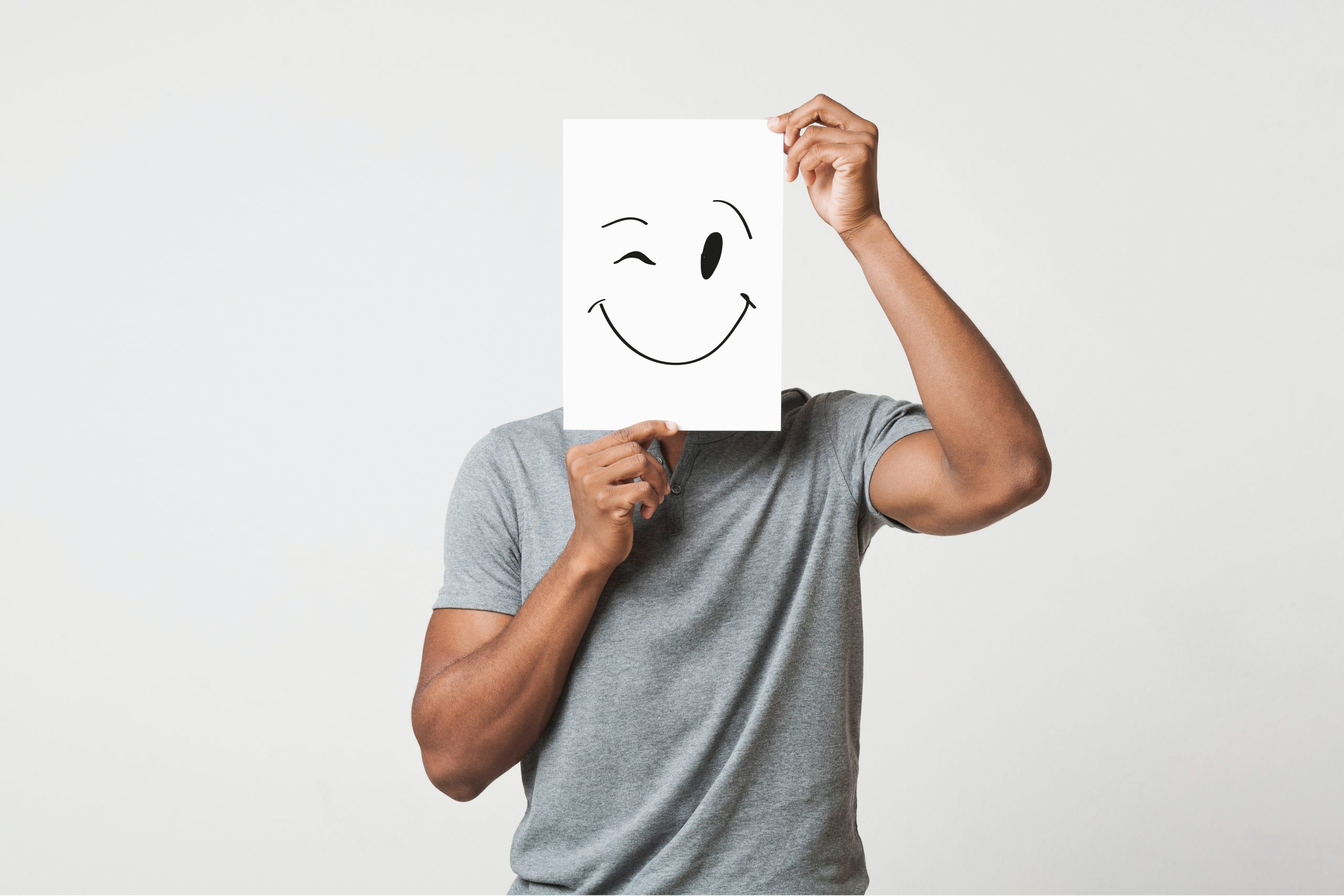 Black man cover his face with happy and winking smiley drawn on paper, white studio background